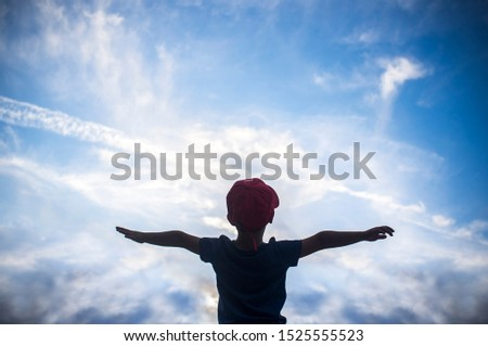 4 years old boy pretending to fly over cloudy sky. Encourage children Imagination concept #1525555523