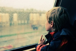 7 years old boy sitting in the train and looking to the rain