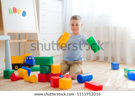 5 years old boy sitting on the floor playing with colorful plastic blocks. Creativity educational toys for preschoolers #1111912016