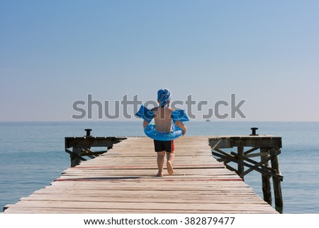 3 years old boy walking on beach wooden pier ready to swim in a sea. Summer outdoor activities with children on the beach. Blue sky and ocean in the morning. Safety first.