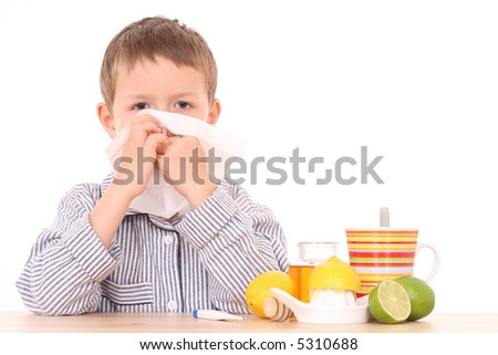 5-6 years old boy with thermometer and cold and flu remedy