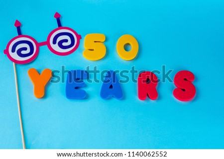 50 years old celebrating classic logo. Colored happy anniversary 50 th colored numbers on blue background. Greetings celebrates card. Traditional digits of ages. Flat lay . #1140062552