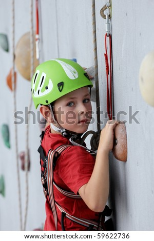 6 years old child climbing on a wall in a climbing center.