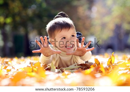 5 years old child lying on the golden leaf - stock photo