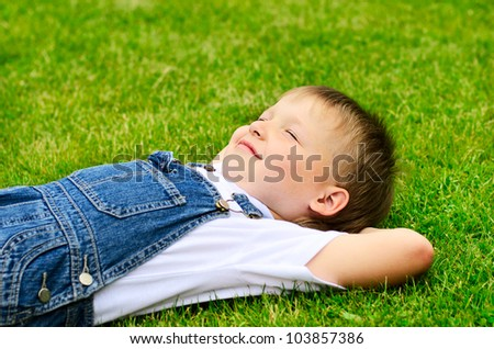 4 years old child lying on the grass.
