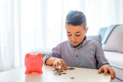 7 years old child sitting st the table with money and a piggybank. Happy boy with euro coins. Close up Little boy saving money in piggy bank focus on piggy bank