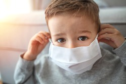 2-3 years old child wearing surgical mask. Little boy trying to stay healthy by wearing a mask to protect him against corona virus covid-19 / 2019-nCov. Boy wearing anti virus mask staying at home