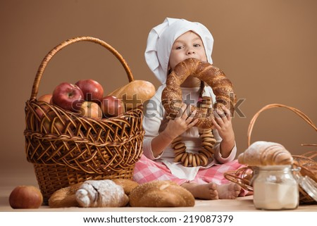 5 years old girl baker eating bakery products, studio shot