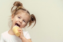 3-4 years old girl in a white T-shirt eating ice cream and smiling. children and sweets