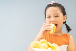5 years old girl.Little asian thai kid girl eating durian fruit at home.She make every happy and yummy face.First time with durian.Durians are the king of fruits.Asian girl holding durian on plate.