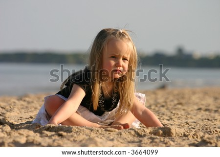 stock photo : 3 years old girl sitting on a beach.