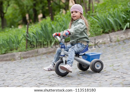 4 years old girl wearing jeans, pink cap and green coat rides on tricycle