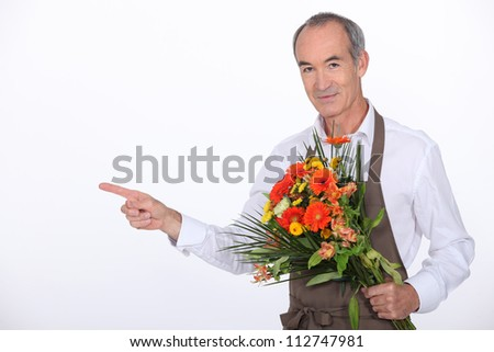 65 years old male florist taking a flowers bouquet and pointing finger on something