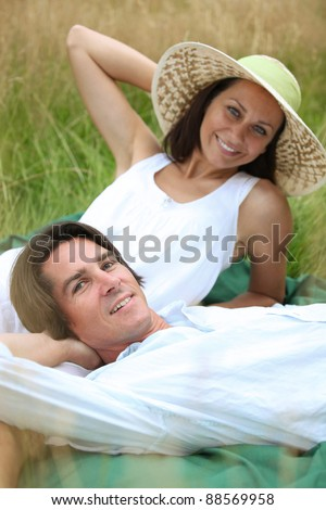 40 years old man and woman relaxing and  lying down in a meadow - stock photo