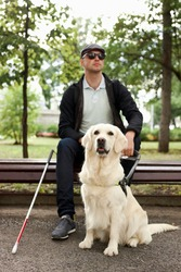 25 years old man suffer from blindness, get help by dog guide, sit having rest outdoors