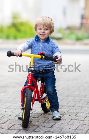 2 years old toddler boy having fun on bicycle in summer