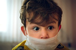 3 years old Turkish baby wearing surgical mask peering anxiously at one point