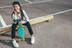 11-12 years old tween girl wearing fashion sportswear rollerskating on skateboard in the city street, urban hipster style