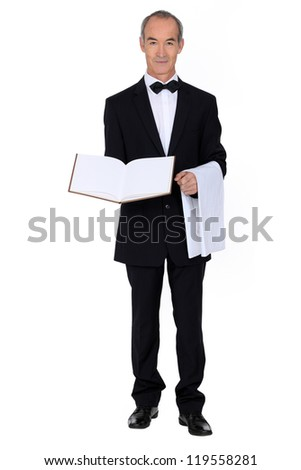 60 years old well dressed waiter is presenting a visitor book or a menu