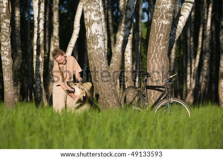 50 years old woman in straw hat playing with dog in  birch forest at summer