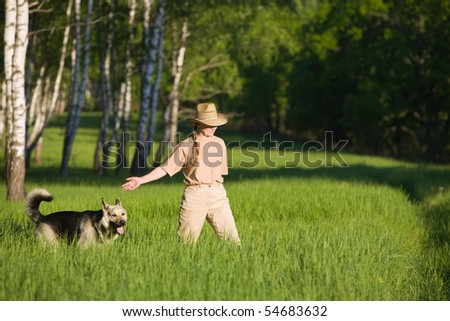 50 years old woman in straw hat walking with dog in  birch forest at summer
