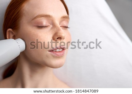 20-25 years old woman receiving a non-surgical rejuvenation procedure, RF face lifting with the use of electric device equipment. hardware facial massage Foto stock ©