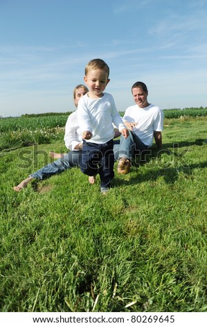 2 years young boy and parents running through meadow