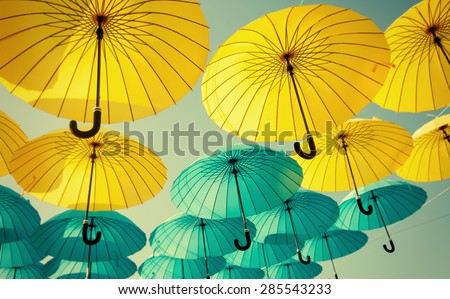yellow and blue umbrellas under the beautiful cloudy sky. color