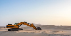 yellow bulldozer machine removing sand from Corralejo dunes in Fuerteventura, Canary Islands