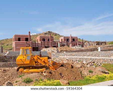 yellow bulldozer on construction of villas on the island