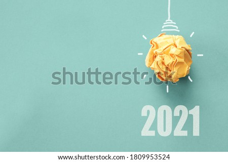2021 Yellow paper light bulb on blue background, innovative business vision and resolution , biofuel clean energy concept