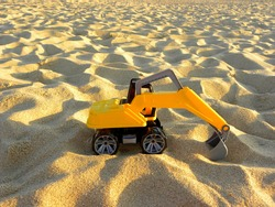 Yellow plastic excavator in the sand. Toy construction equipment. Children's toys on the beach.