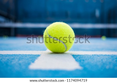 Yellow tennis balls in court on blue turf