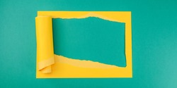 Yellow torn paper frame on green background with place for text in the middle, top view close-up.