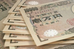 10000 yen Japanese notes. Background or wallpaper with reduced contrast and color saturation. A bundle of bills. Backdrop on the theme of banks, finance and the economy of Japan
