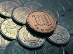 100 yen lies on a pile of Japanese 1 yen coins. Dramatic dark illustration on a financial theme. News about the economy, business and the Central Bank of Japan. Scratched and dilapidated money. Macro