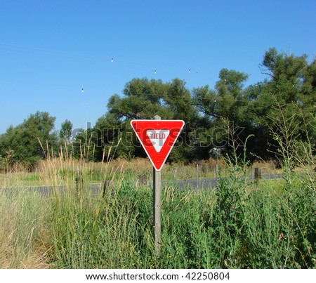 yield sign in country field - stock photo