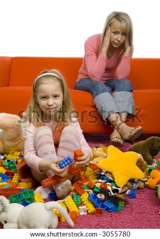 5-6yo girl with her toys on the floor. There's huge mess. There's mother sitting on couch behind girl. Mother has headache cause this mess.