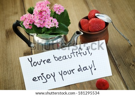 """""""You're beautiful, enjoy your day"""" inscription on the background of the cup with strawberries"""