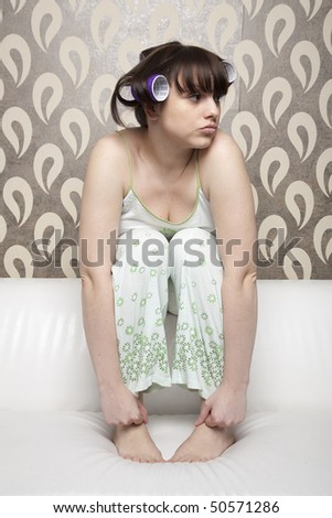 young adult girl with hair rollers sitting at white sofa and looking