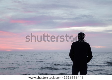 Young adult man in warm black overcoat standing alone and staring at small waves of sea and overcast sky. Peaceful atmosphere in winter evening. Back view. Empty place for text, quote or sayings.