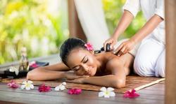 Young Asian woman enjoying a hot stone massage