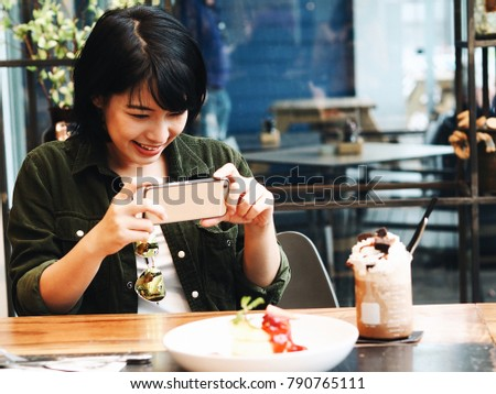 Young Asian woman take a photo by smart phone and joyful with delicious pancake and dessert in coffee shop.