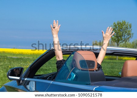 Young attractive brunette woman sitting with her hands up in Luxury Convertible Sports Car - rear view #1090521578