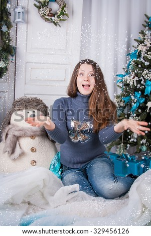 Young beautiful  girl is happy new year holiday. A girl sits among Christmas trees and snowmen, and happily throwing up hands artificial snow. New Year - the most cheerful and desirable holiday