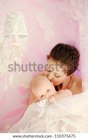 Young beautiful mother kissing her small sleeping newborn baby - indoors