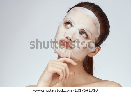 young beautiful woman in a face mask, skin care                               #1017541918