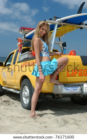 Young Blond girl on the beach of CA with Lifeguard car