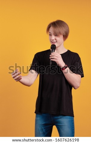 Young boy teenager in a black T-shirt with a microphone in his hands sings and speaks, on a yellow background Stockfoto ©