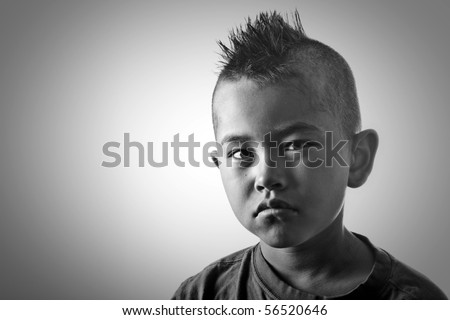 Young boy with funny mohawk haircut and serious look in black and ...